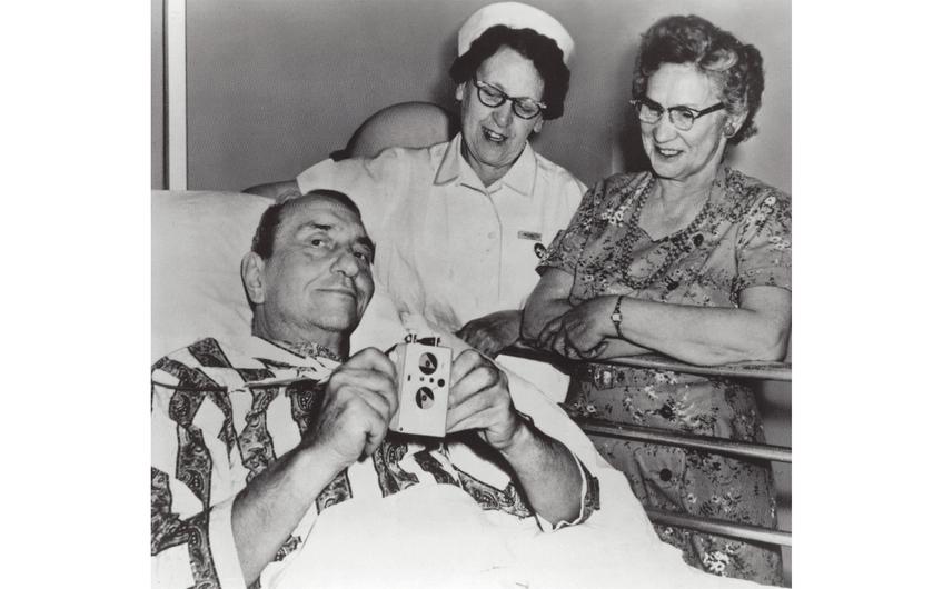 Warren Mauston zeigt seinen Herzschrittmacher mit Krankenschwester und Frau. 1959 war Mauston der erste US-Patient, der mit einem externen Herzschrittmacher versorgt wurde