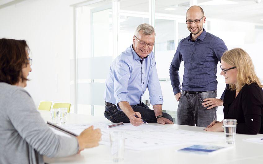Teambesprechung mit Plan: Die Erfahrung und die Fachkompetenz der  interdisziplinären Teams gehören zu den Erfolgsfaktoren der ITB GmbH Foto: ITB GmbH