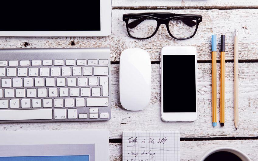 Auch wenn das papierlose Büro noch Zukunftsmusik ist, sind Computer und Smartphones heute auf den meisten Schreibtischen zu finden (Foto: © Halfpoint – stock.adobe.com)
