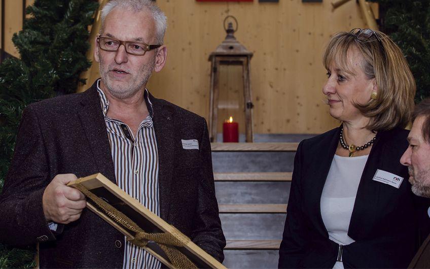 Andreas Lemm von der Zimmerei Lemm & Overberg (l.) überreichte Caroline Hartmann-Serve und Martin Serve eine Urkunde, die bescheinigt, dass der Neubau die Atmosphäre um circa 300 Tonnen CO2 entlastet