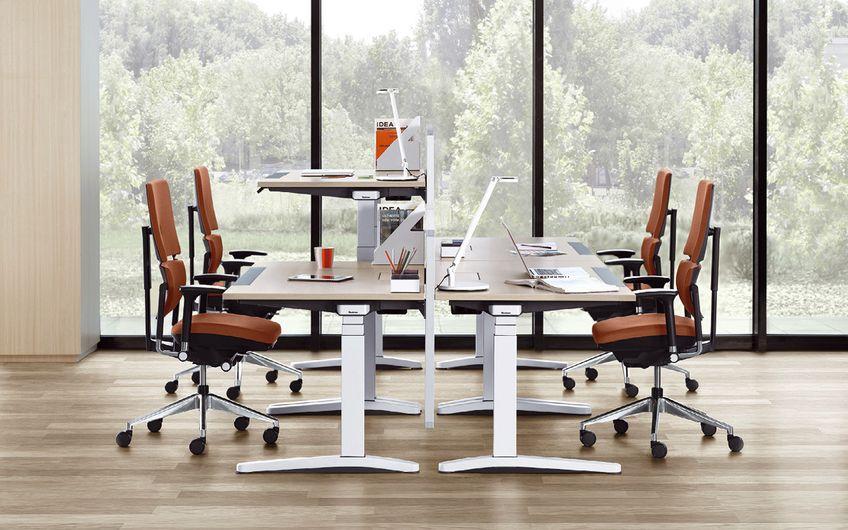 Drei Personen sitzen, eine steht: ein Beispiel für modernes Arbeiten im Büro
