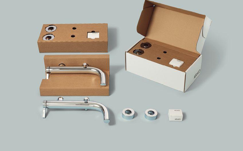 Versandverpackung für eine schwere Badewanneneinlassarmatur inklusive Zubehör nach Hausstandard des Kunden; zweiteilige Wellpappen-Inneneinlage, welche die Teile fixiert, ordnet, sichert und schützt
