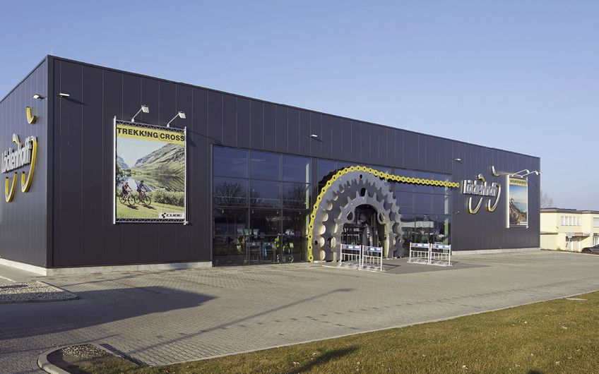Das Gebäude wirkt von außen und innen sehr modern. Den Eingangsbereich zieren überdimensionale Kettenblätter (Foto: Löckenhoff + Schulte)
