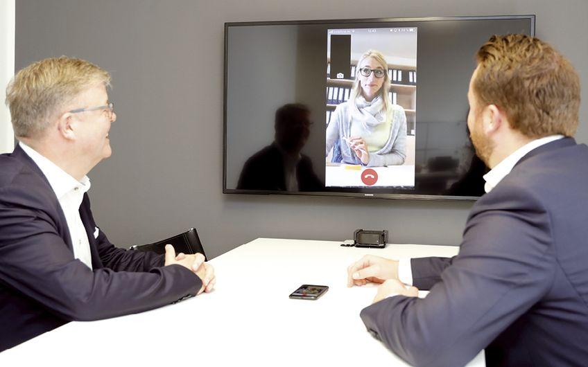 Vater und Sohn konferieren via Skype mit ihren Kunden